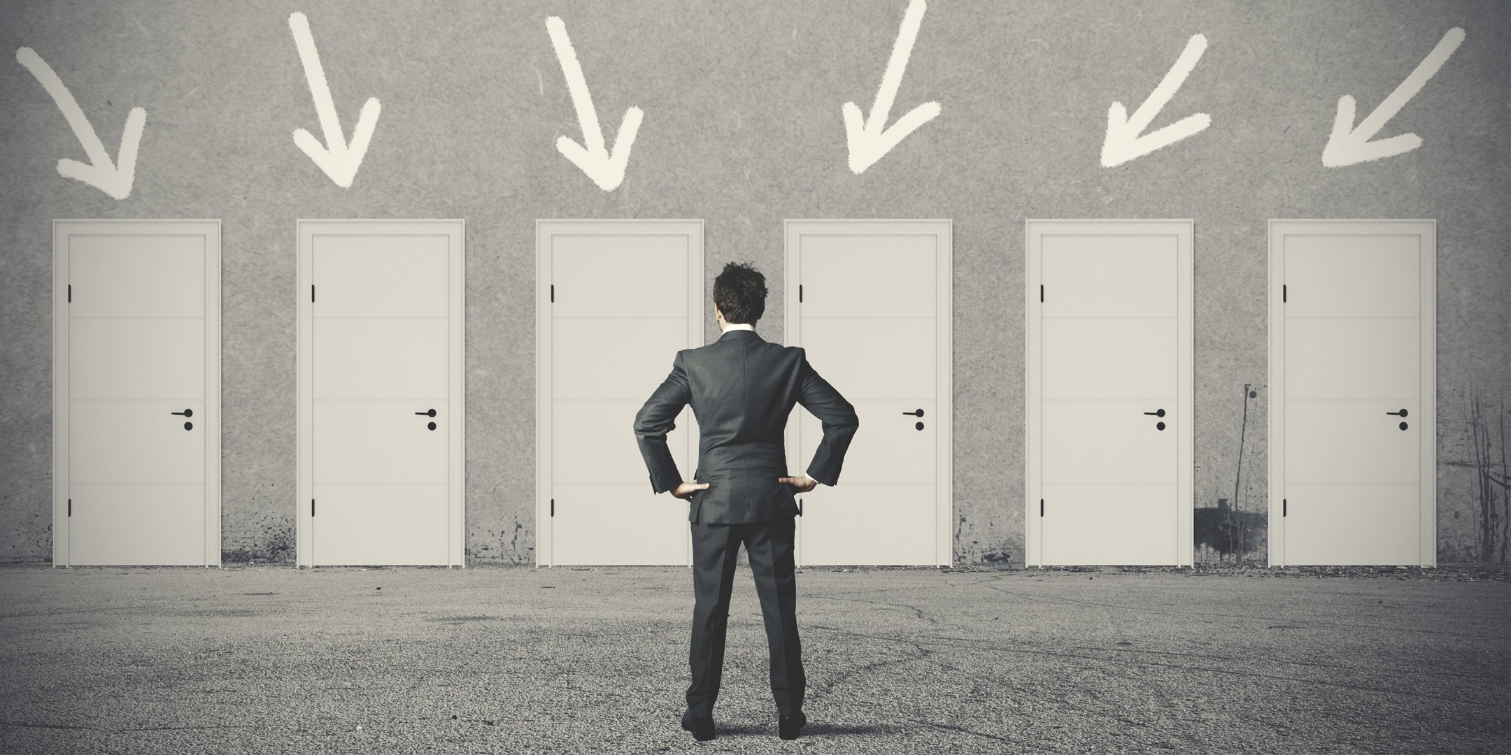 Man standing in front of doors choosing which one to go through.