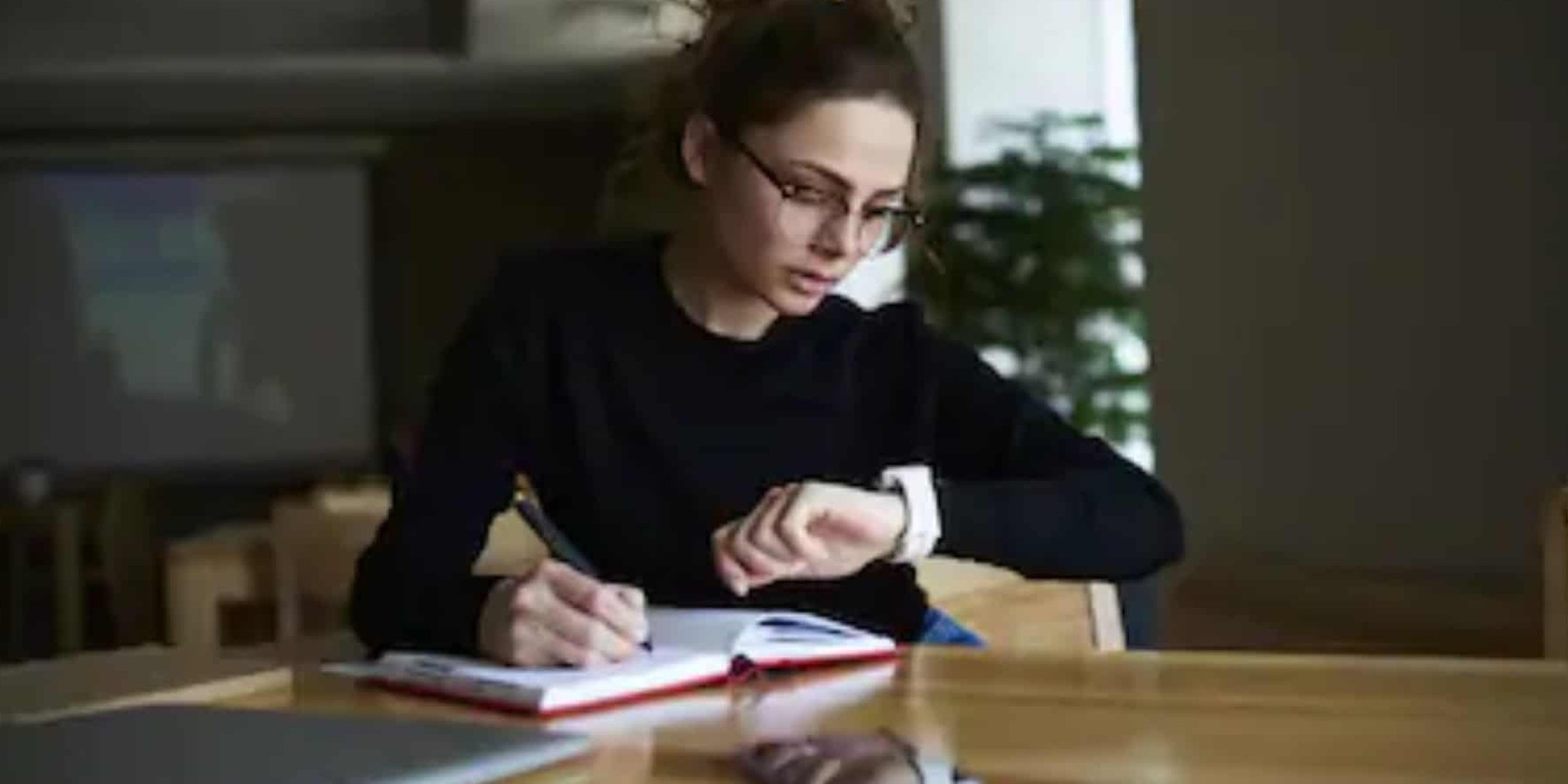 A woman looking at the time on her watch whilst writing a to-do list.