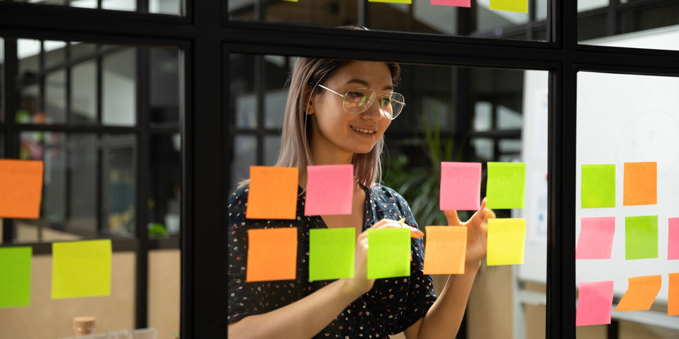 A lady creating a high-level plan on a glass window with sticky notes.