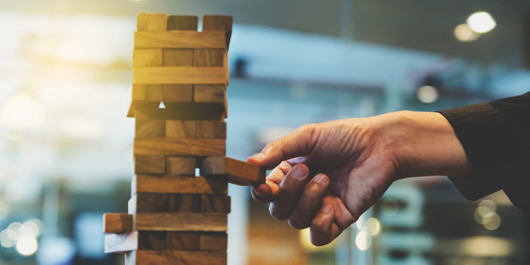 A person playing jenga with the risk of it falling.