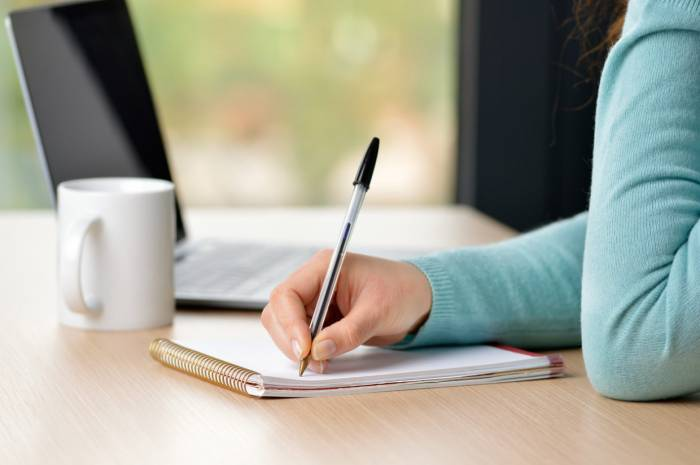 Female hand writing notes in a notebook on a desk at office