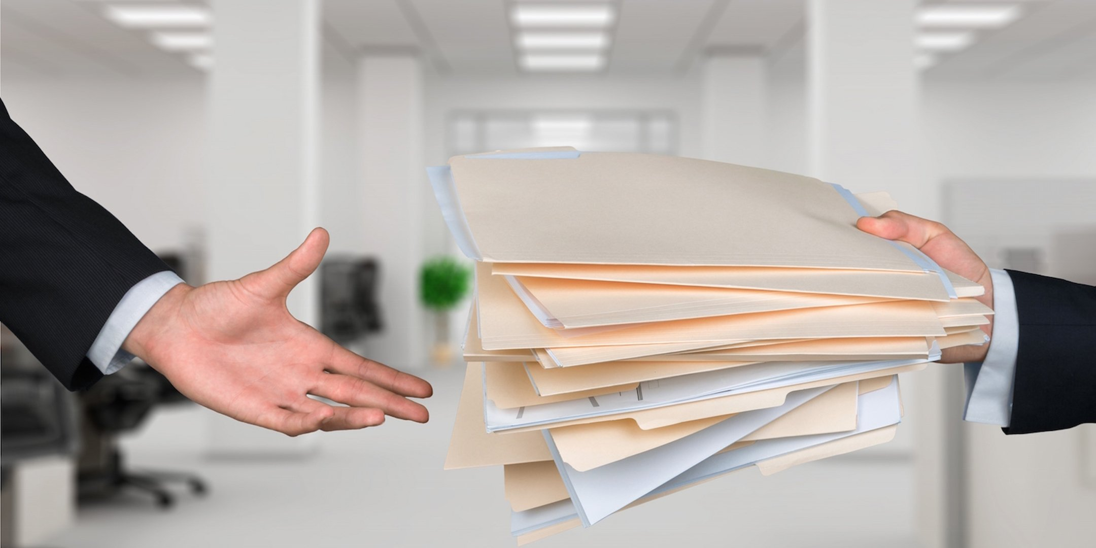 Person handing files of documents over to another person.